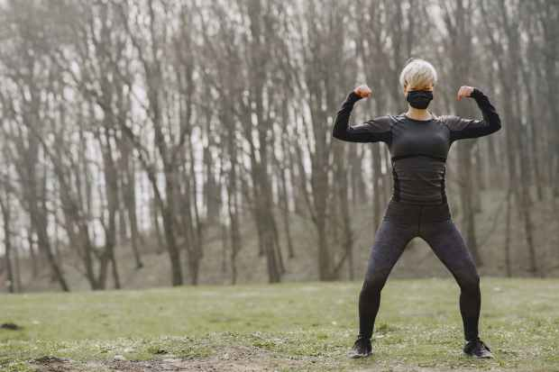 athletic sportswoman performing front double biceps pose in park